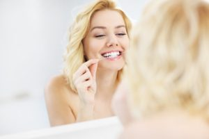 a young woman flossing her teeth while standing in front of a mirror