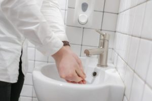 a dental in Phoenix washing their hands before offering care to a patient