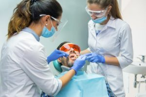 a dentist in Phoenix and her assistant performing an exam on a male patient's smile