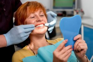 a middle-aged woman with red hair admiring her new smile in the mirror at the dentist's office