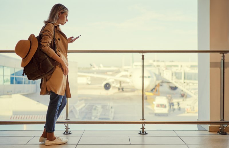 a woman with her bag, hat, and phone waiting to board a plane at the airport