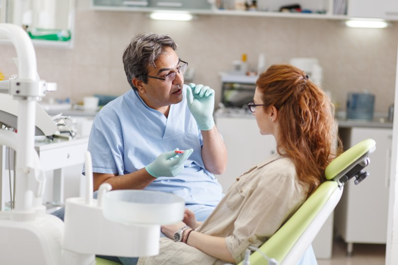 a dentist talking to a young female about replacing a back tooth