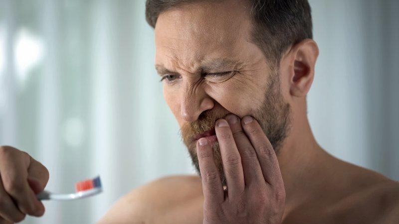 an older man brushing teeth and discovering he has gum disease in Phoenix